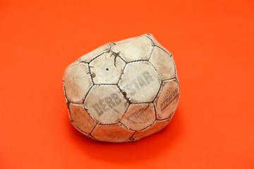 Alter, beschaedigter und verbeulter Fussball aus Leder