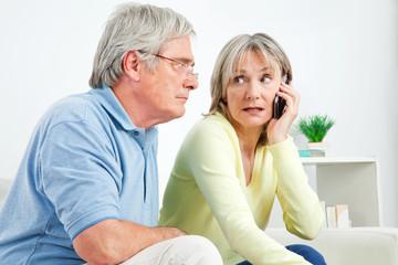 Seniorin telefoniert mit Handy neben Senior