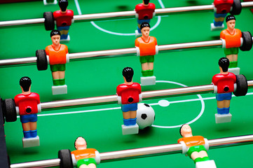 soccer table game with green field and football players