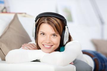 lächelnde frau mit kopfhörern auf dem sofa