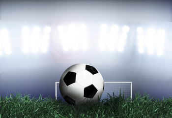 Soccer ball on grass field with spotlights