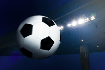 Soccer ball and illuminated stadium at night