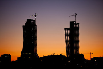 City silhouette during sunset with construction sites and cranes