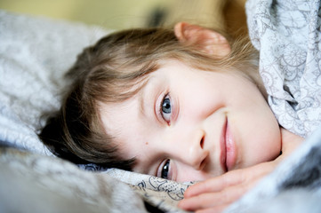 Adorable little girl resting in the bed
