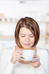 frau trinkt kaffee mit geschlossenen augen