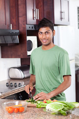 happy young man cooking in kitchen