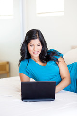attractive young woman using laptop on her bed