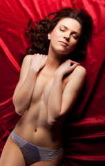 Young naked girl lay on red - close breast hands