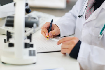 Closeup on hands of medical doctor working with documents