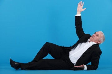 A mature businessman lying on the floor.