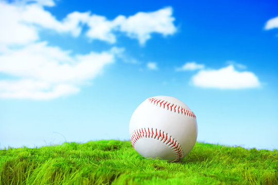 base ball in green grass field with sky