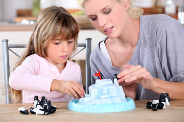 mother an daughters playing with small penguins figurines