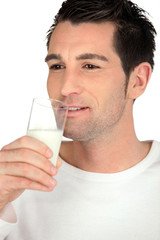 Young man drinking a glass of milk