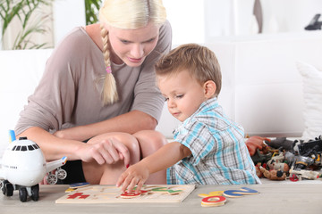 Little boy and young woman playing to puzzle