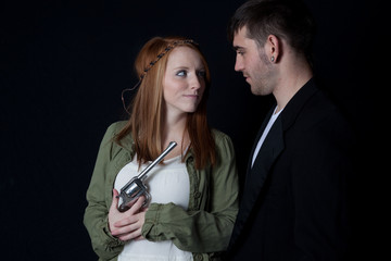 couple together, she is holding a gun