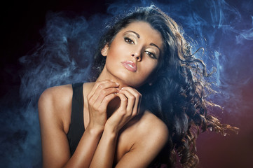 Portrait of young seductive woman in the blue smoke on the black