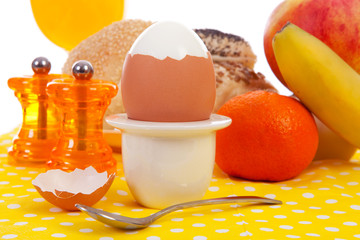 Breakfast with peeled egg, delicious bread and fruits