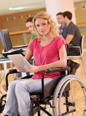 Young woman in wheelchair working in office