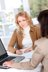 Beautiful woman signing contract in insurance company