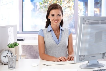 Smiling office worker using computer