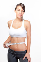 Happy woman with abs measuring waist