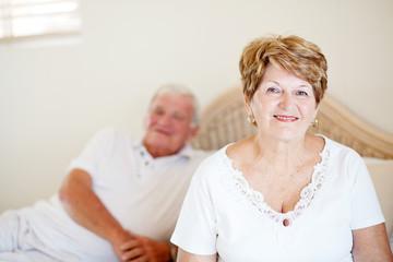 senior couple sitting on bed