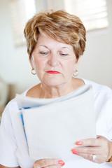 elderly woman reading newspaper