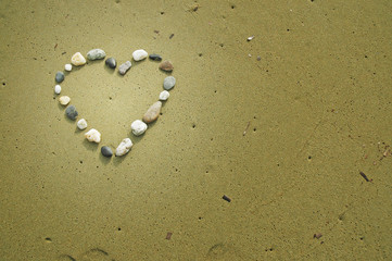 Heart made of small stones on sand