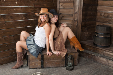 brunette and blonde CowGirls sitting in old depot