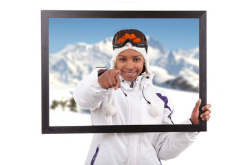 Young smiley woman in ski gears  holding a picture frame