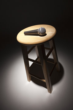 Microphone Laying on Wooden Stool Under Spotlight