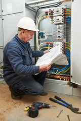 Electrician at wiring with working drawings