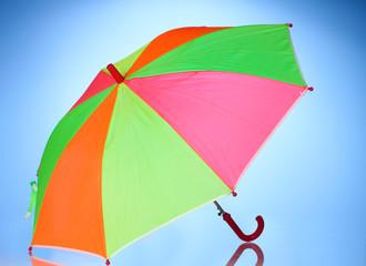 Multi-colored umbrella on blue background