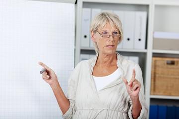 seniorin hält vortrag am flipchart