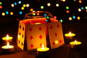 Candles and playing cards on wooden table on bright background