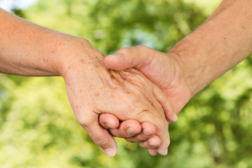 Closeup of old people hands holding together