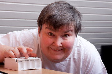 Geistig behinderte Frau mit Tablettenbox blickt positiv