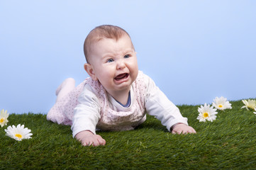 crying baby lying on a grass field