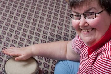 Geistig behinderte Frau trommelt auf Bongos und ist glücklich