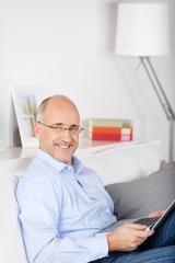 lächelnder mann sitzt mit laptop auf dem sofa