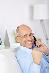 glücklicher mann am telefon ballt die faust