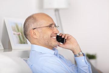glücklicher mann telefoniert zuhause