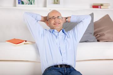 entspannter mann sitzt zuhause vor dem sofa