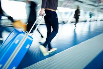 People walking along an airport corridor