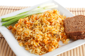 Rice with green onions and brown bread on a white square plate