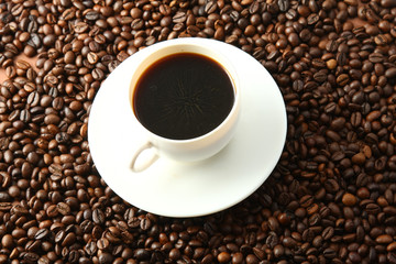 a cup of coffee on coffee beans, from above