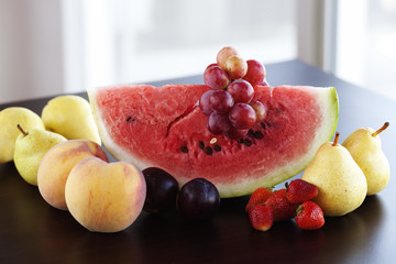 watermelon, strawberry, grape, plum and pear lying on a wooden t