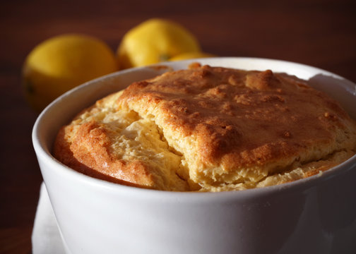 Baked cheese soufflé portion in a ramekin with lemons