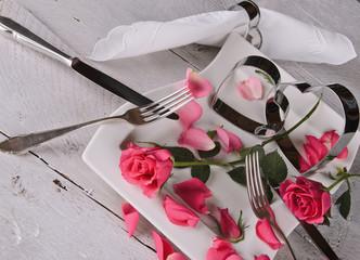 Festliches Gedeck zum Valentinstag auf rustikalem, weißem Tisch
