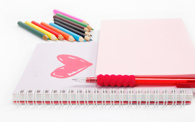 Notebook and colored pencils on a white background.